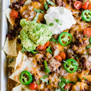 Sheet pan nachos topped with juicy ground beef, beans, cheese, jalapeño, tomato, sour cream and guacamole.