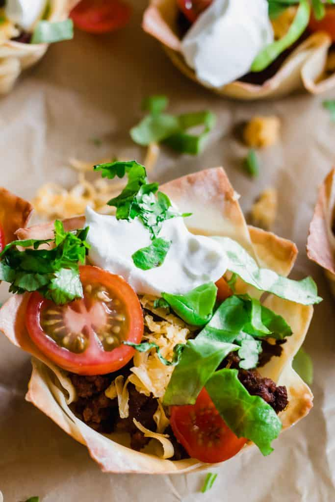 Taco Cups filled with uicy taco meat, melty cheese, shredded lettuce, tomato and sprinkled cilantro.