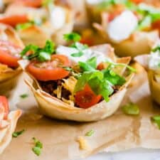 Taco cups. Crunchy wonton cups filled with uicy taco meat, melty cheese, shredded lettuce, tomato and sprinkled cilantro.