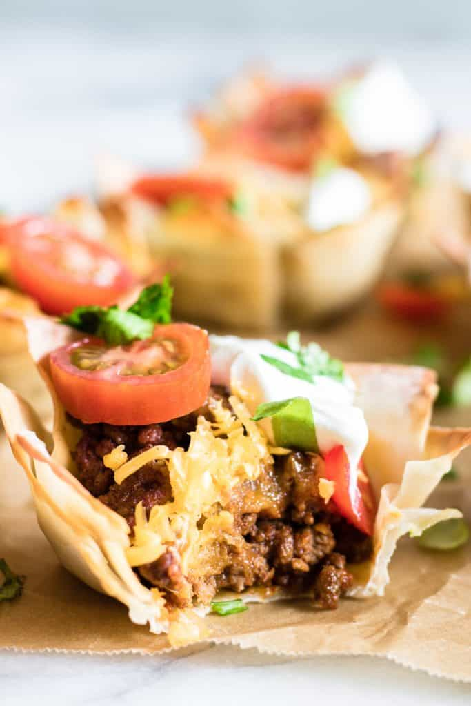 Bit into Taco Cup showing juicy taco meat, melty cheese, shredded lettuce, tomato and sprinkled cilantro.