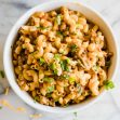 White bowl filled with cheesy one pot taco pasta topped with cilantro.