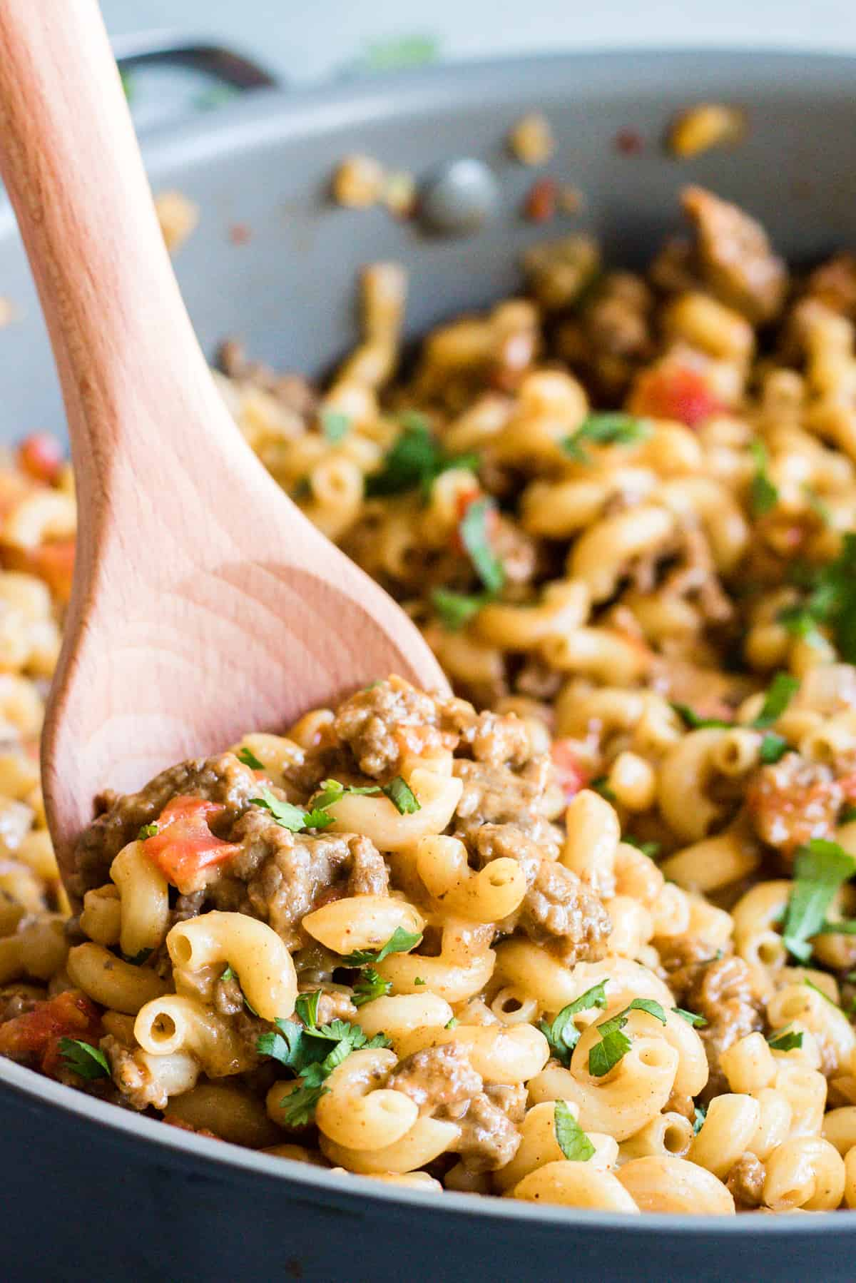 Wooden spoon scooping up cheesy one pot taco pasta, loaded with beef and tomatoes. Sprinkled with cilantro.