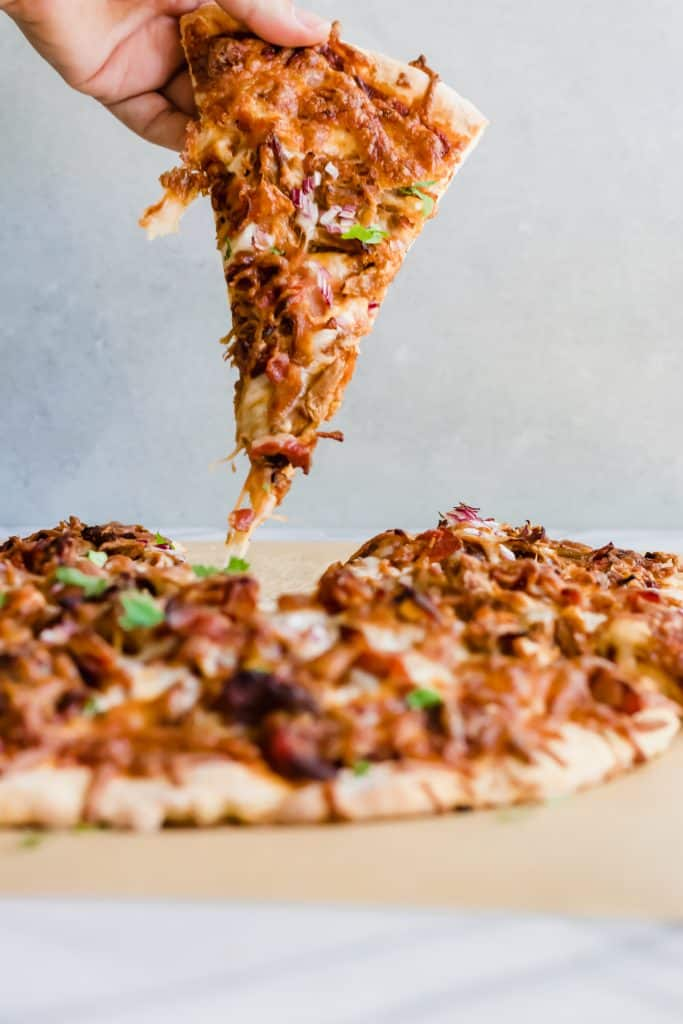 Pulled Pork Pizza. Pizza layered with BBQ sauce, cheese, pulled pork, bacon and red onion. Cut into slices.