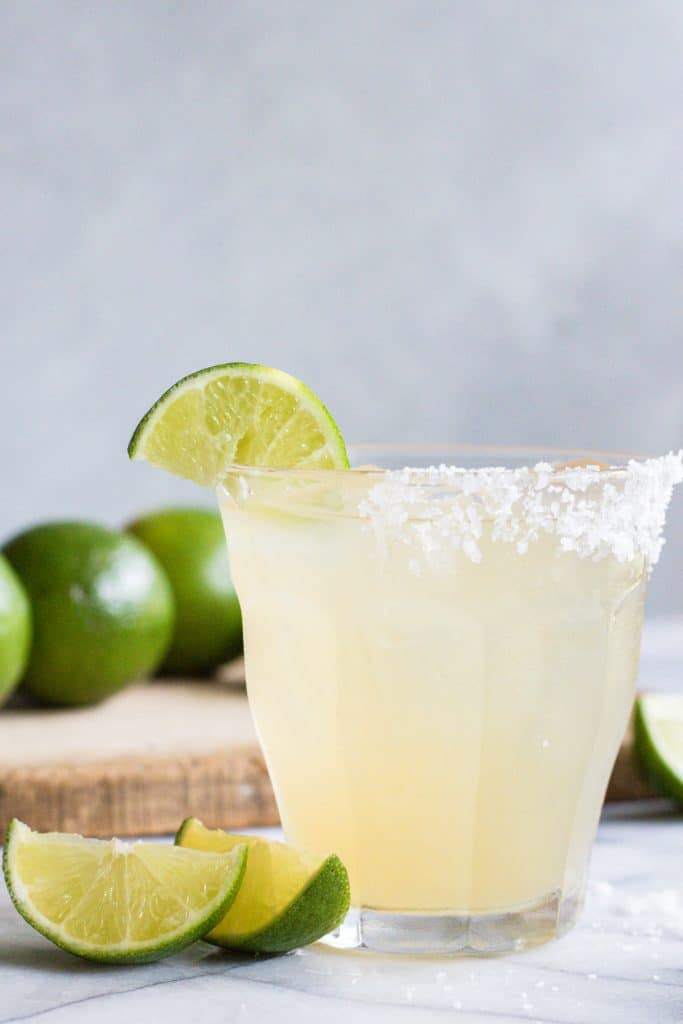 Glass with classic margarita on the rocks with a salt rim and lime wedge garnish.