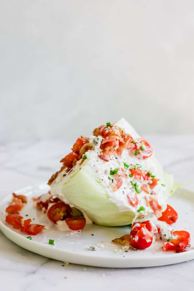 A classic salad wedge on a white plate, topped with diced bacon, tomato and chives.