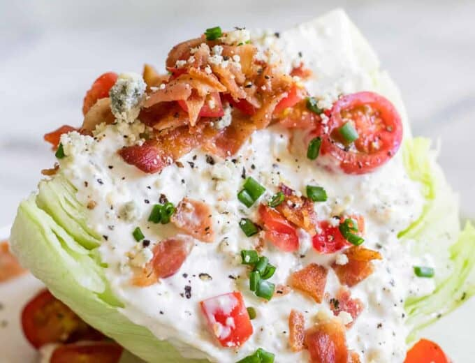 An iceberg salad dressed as a classic salad wedge with blue cheese dressing, bacon, tomato, and chives.