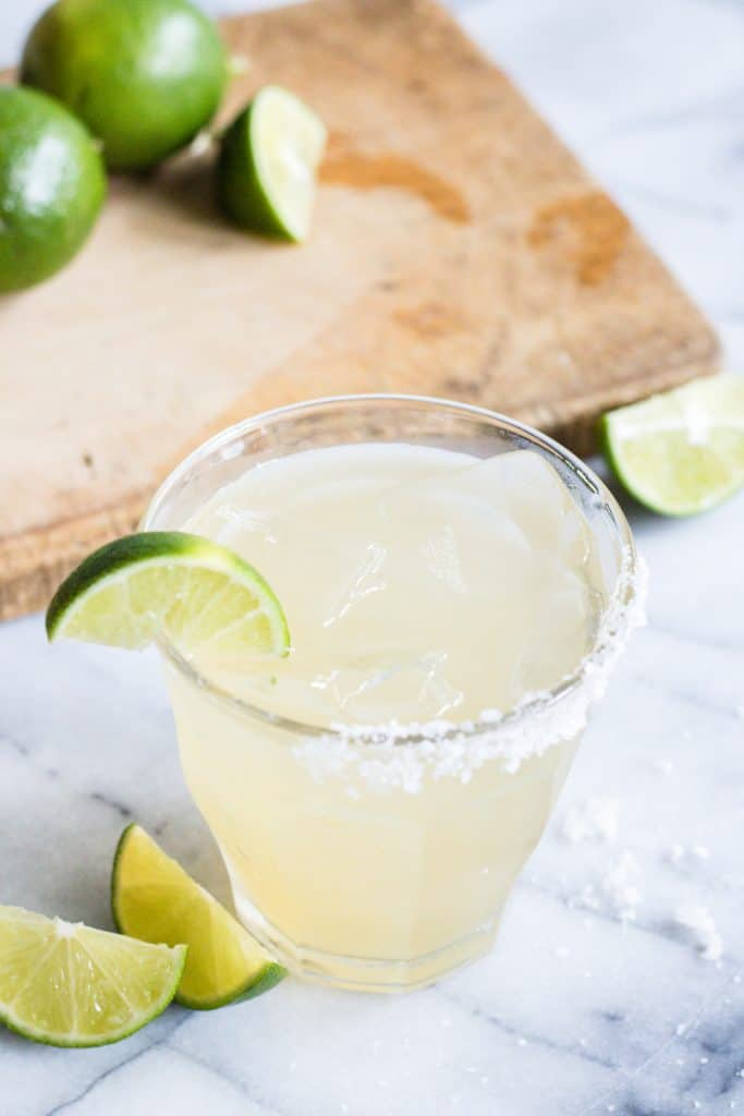 Glass filled with classic margarita, salted rim, and a lime wedge for garnish.