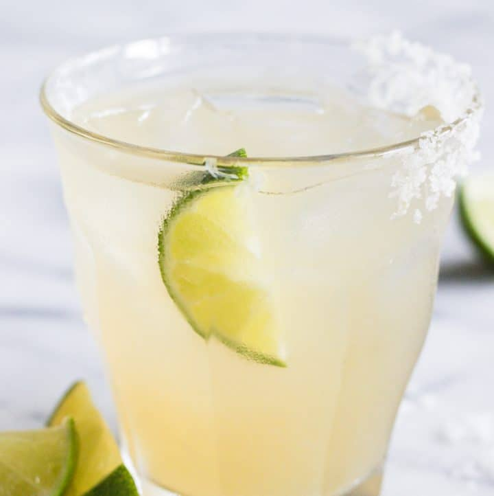 Glass full of classic margarita on ice with a lime and a salt rim.