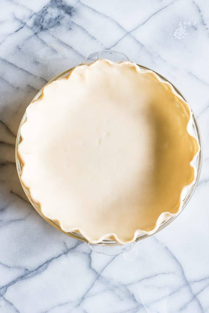 An uncooked pie crust in a glass pie dish. First steps to make a quiche.