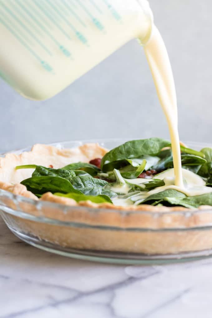 Pouring egg mixture into a pie crust filled with spinach and bacon to make a quiche.