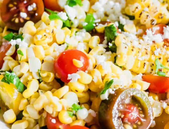 Close up of roasted corn, tomatoes, cilantro, and queso fresco in a roasted corn salad.