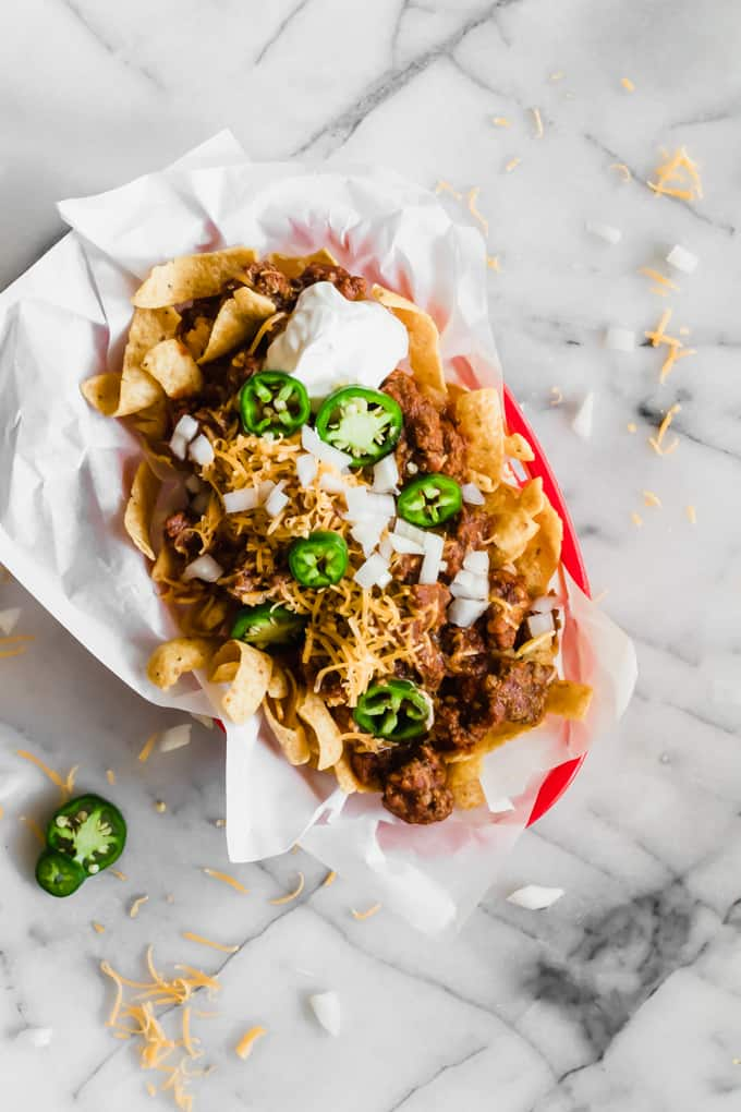 Tray of classic Texas Frito Pie topped with melted cheese, onion, some sour cream and jalapeños.
