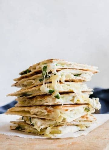 Stack of cheesy spinach and artichoke chicken quesadillas.