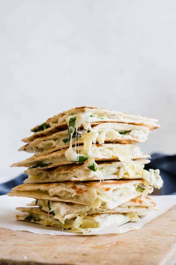 Stack of cheesy spinach and artichoke chicken quesadillas.