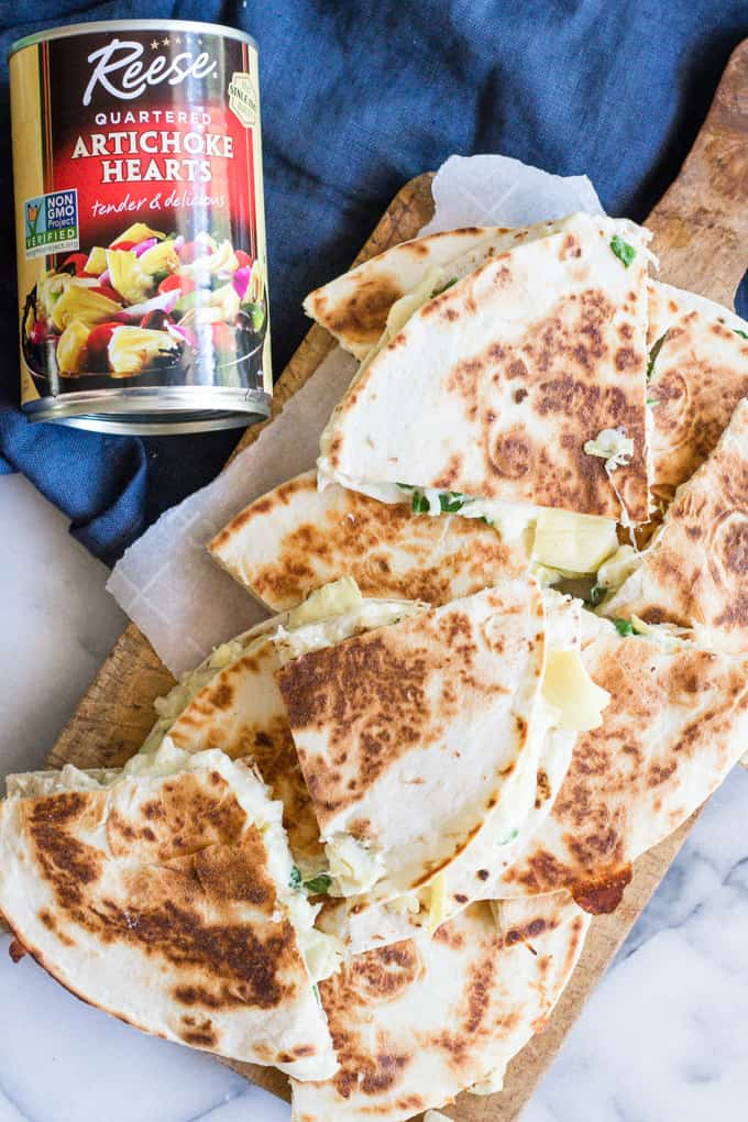 Overhead image of a tray of spinach and artichoke chicken quesadillas with a can of Reese Quartered Artichoke hearts.
