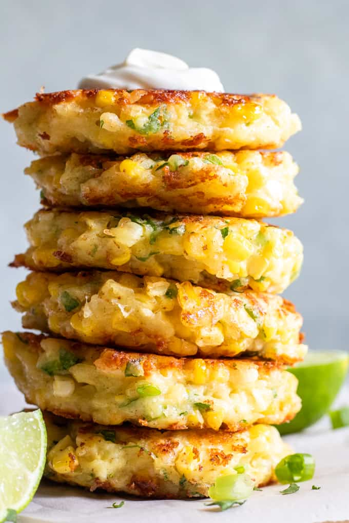 Large stack of cheesy corn fritters topped with a dollop of sour cream.