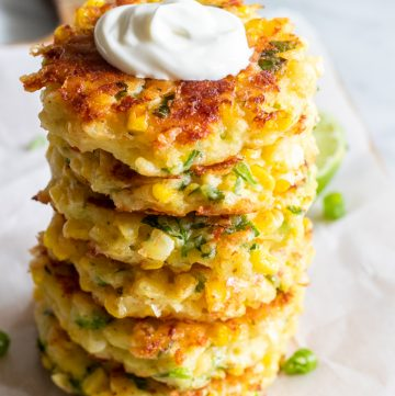 Stack of cheesy corn fritters topped with sour cream.