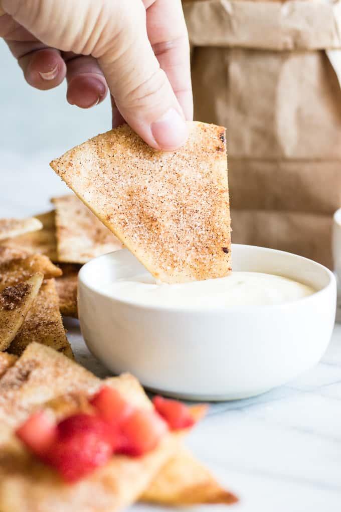 Cinnamon Tortilla Chips dipping into a cream cheese glaze.