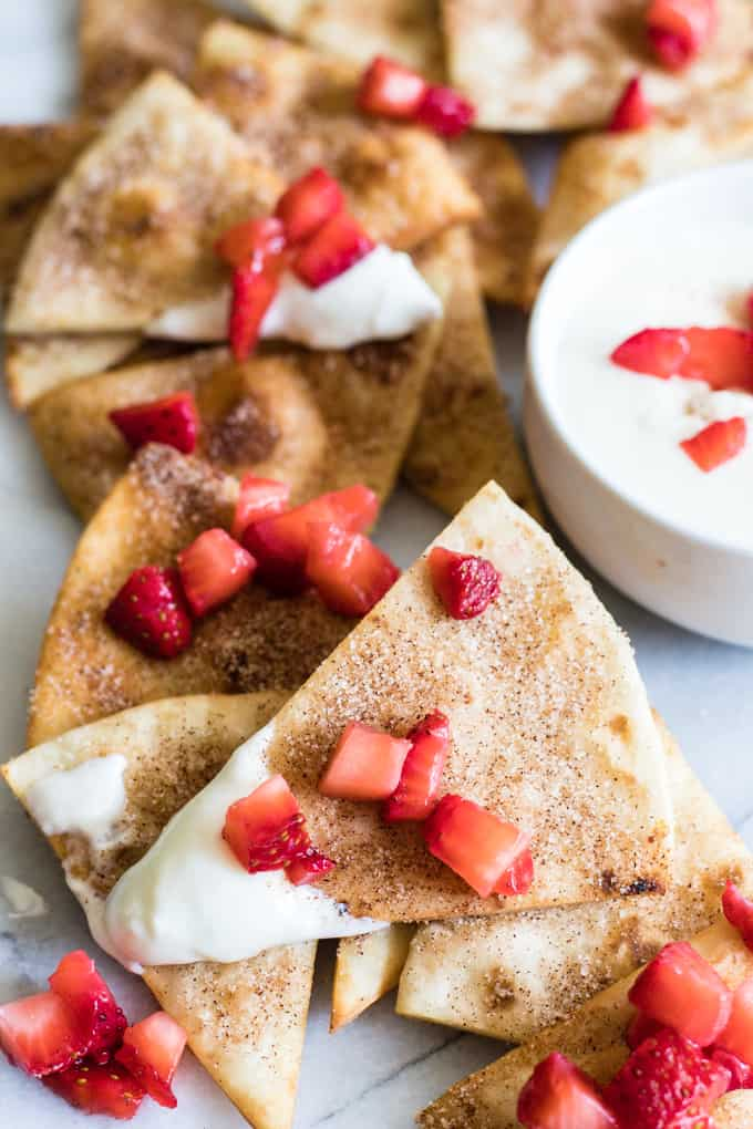 Cinnamon Tortilla Chips dipped into a cream cheese glaze and topped with diced strawberries.