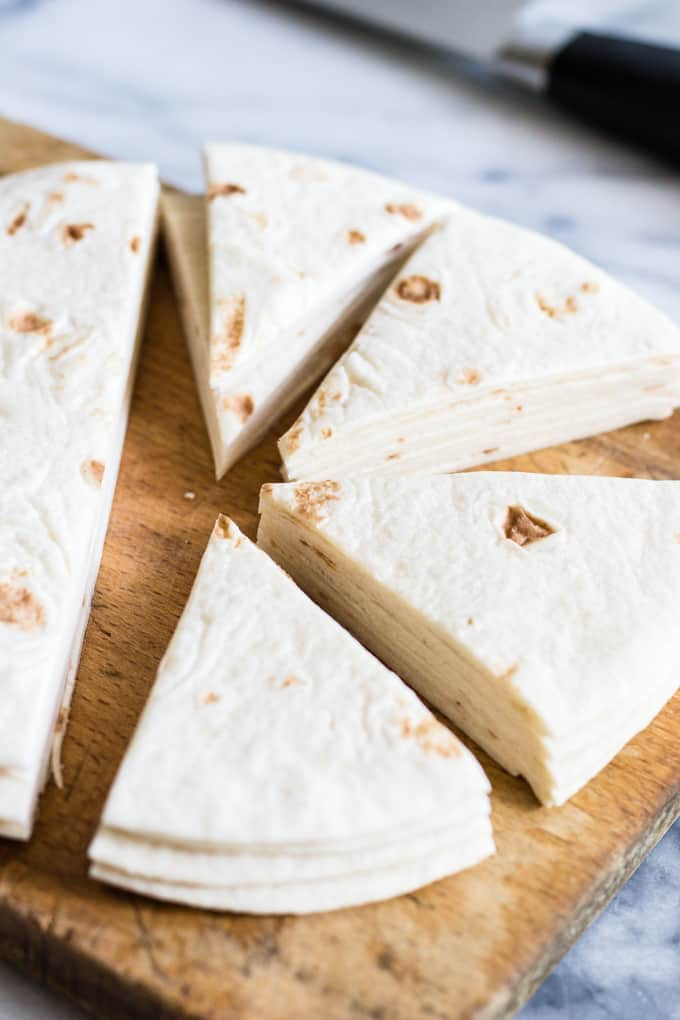 Flour tortillas cut into triangle shapes to be made into cinnamon tortilla chips