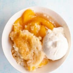 A bowl filled with a serving of peach cobbler, golden yellow peaches, fluffy cake, and a scoop of vanilla ice cream.
