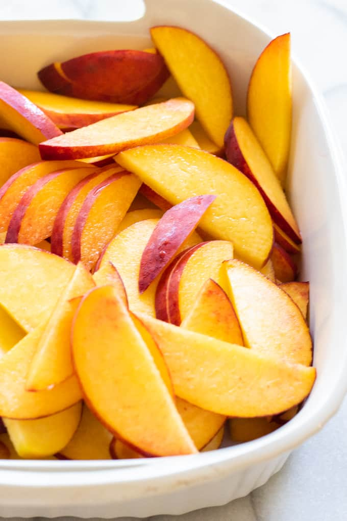 Baking dish loaded with fresh peaches. Sliced and ready to be made into peach cobbler.