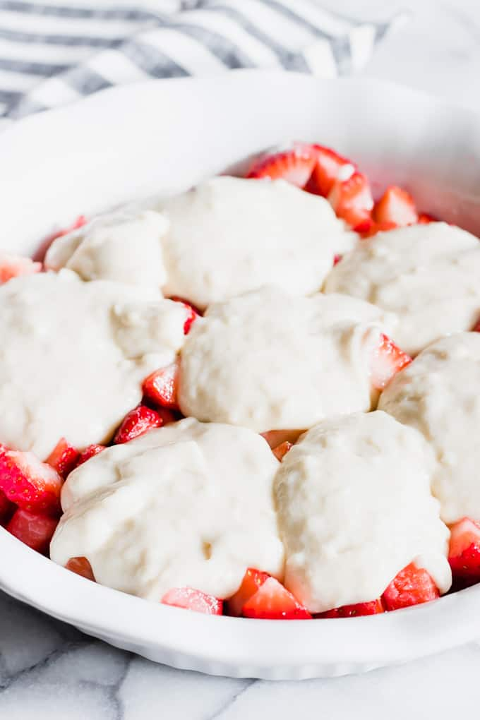 Pie dish filled with fresh strawberries and cobbler batter spooned on top before baking.