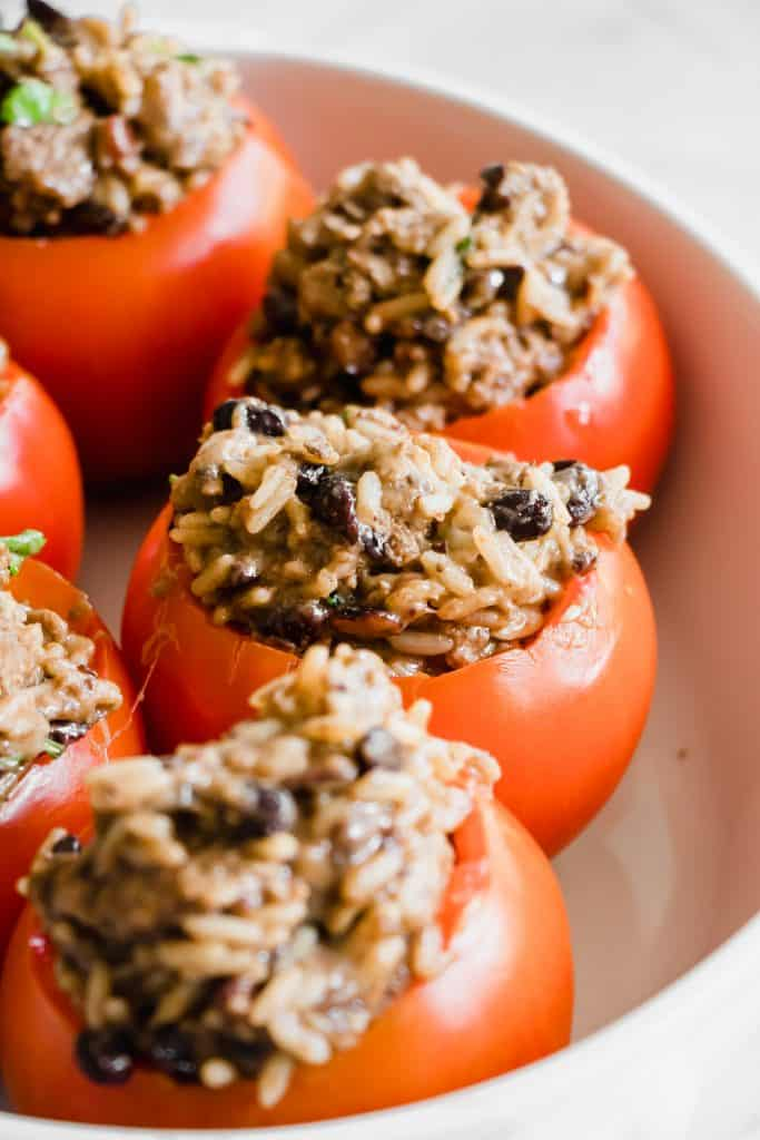 Hollowed out tomatoes stuffed with black beans and rice ready to bake.