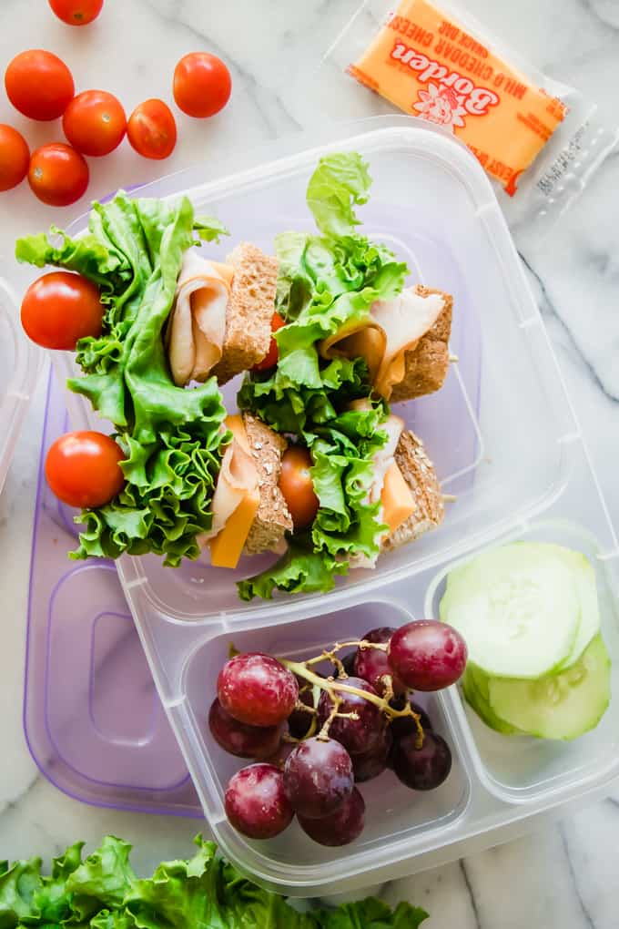 Lunchbox ideas with sandwich kabobs, cucumber, and grapes.