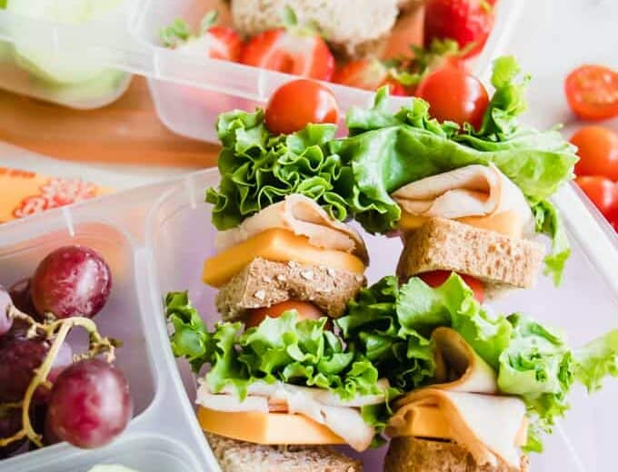 Turkey Sandwich kabobs as a fun kids school lunch idea, sides of cucumber and grapes.