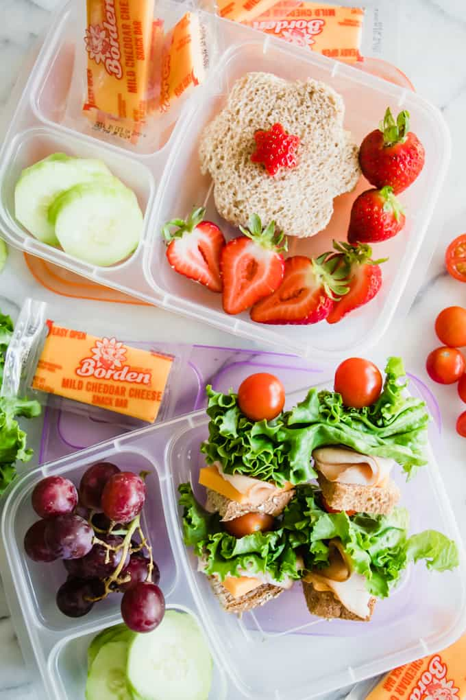 Kid's lunchboxes filled with sandwich kabobs, cucumbers, grapes, strawberries and Borden Cheese Snack bars, giving some fun school lunch ideas.