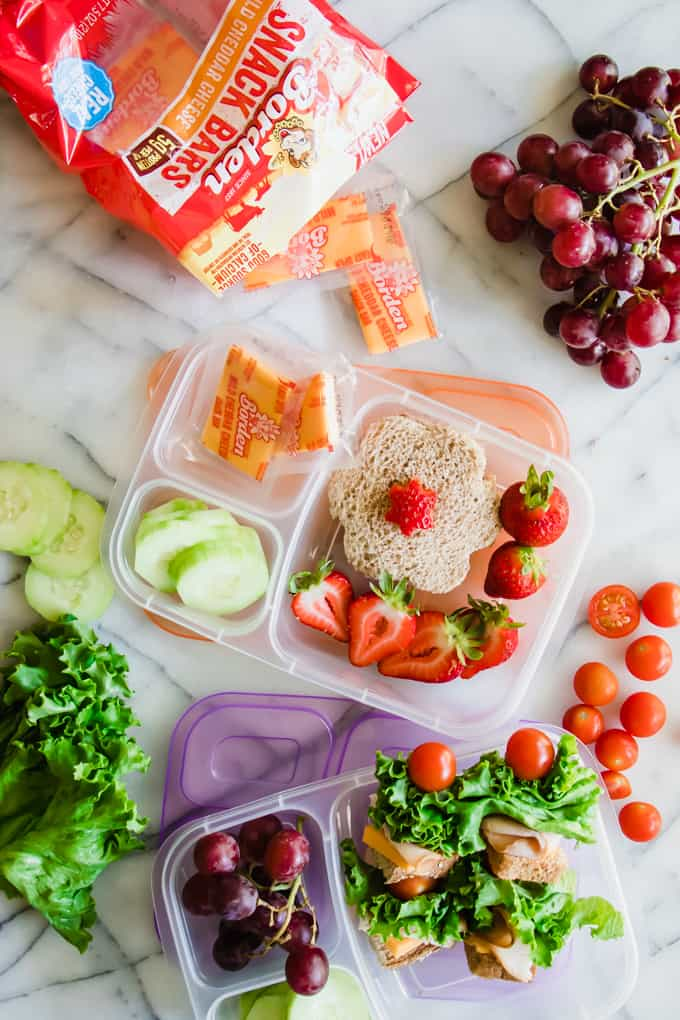 Overhead view of kid's school lunchboxes showing flower shaped peanut butter and jelly sandwiches and sandwich kabobs to give some fun school lunch ideas.