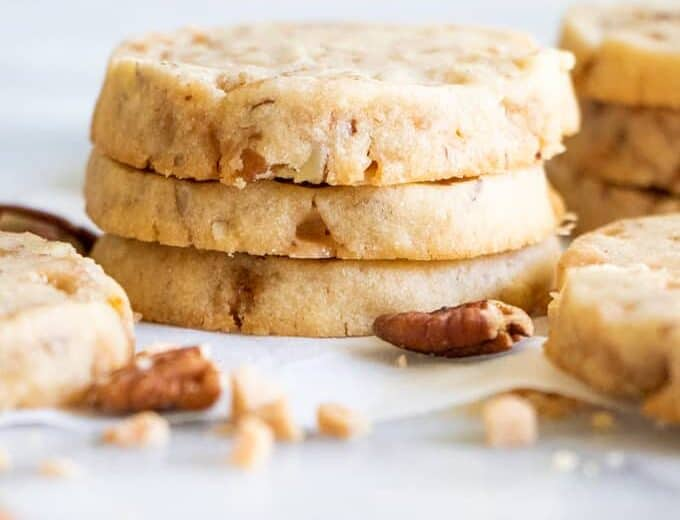 A stack of butter pecan shortbread cookies with bits of pecans and toffee bits around.