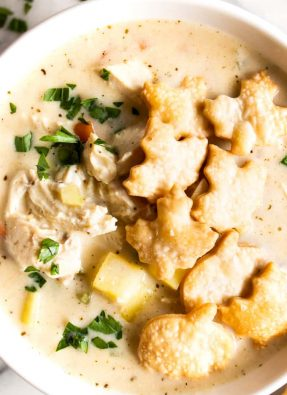 Bowl filled with creamy chicken pot pie soup and topped with pie crust crackers that are shaped like leaves.