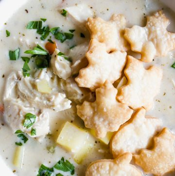 Close up view of chicken pot pie soup, topped with fresh parsley and pie crust crackers.