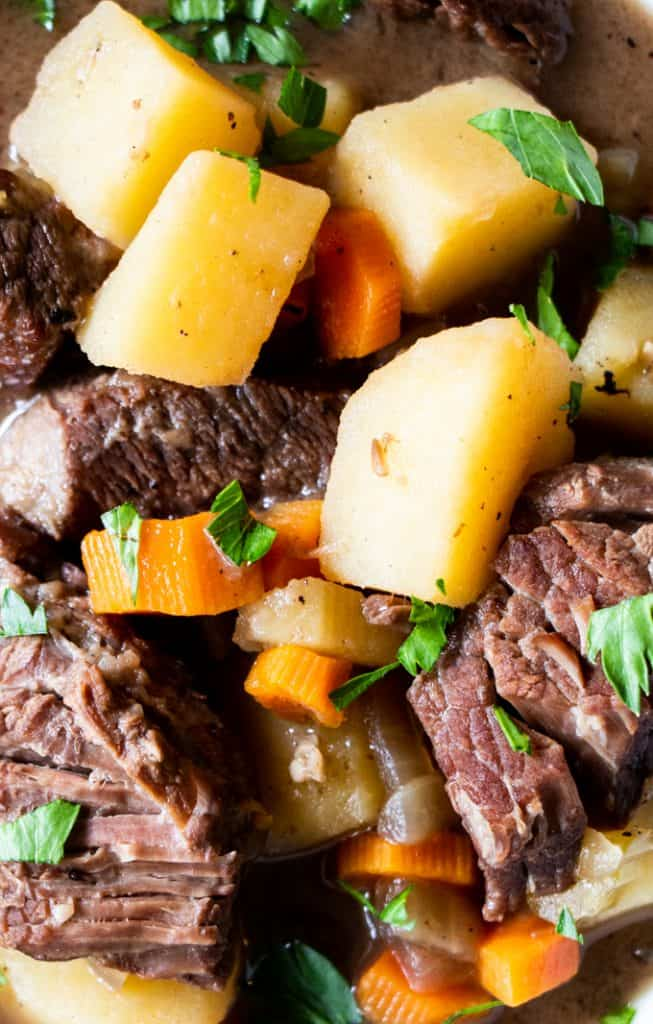 Close up view of chunks of tender meat, chunks of potato, pieces of carrot, all in a classic beef stew.