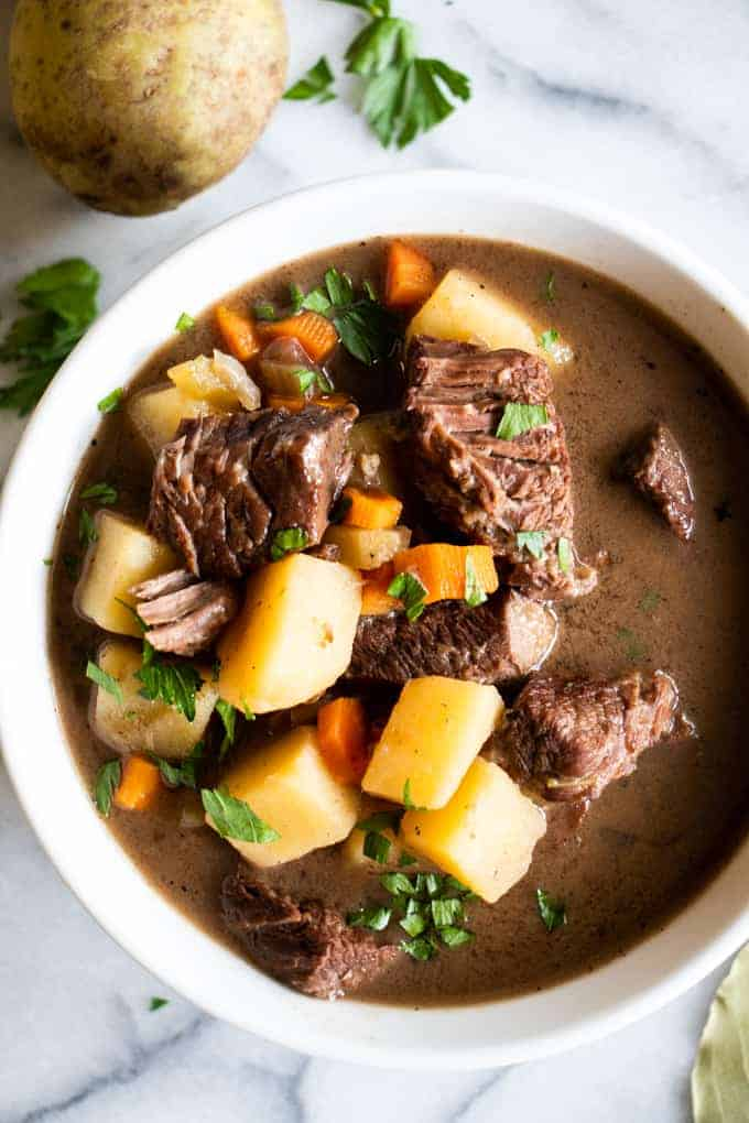 A bowl filled with beef stew, tender meat, flavorful gravy broth. Topped with fresh parsley.