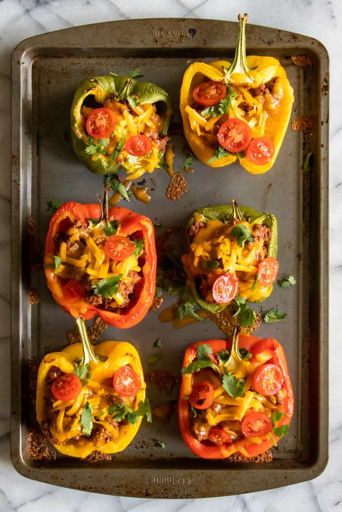 Baking tray filled with halved peppers filled with ground beef taco meat, topped with melty cheese.
