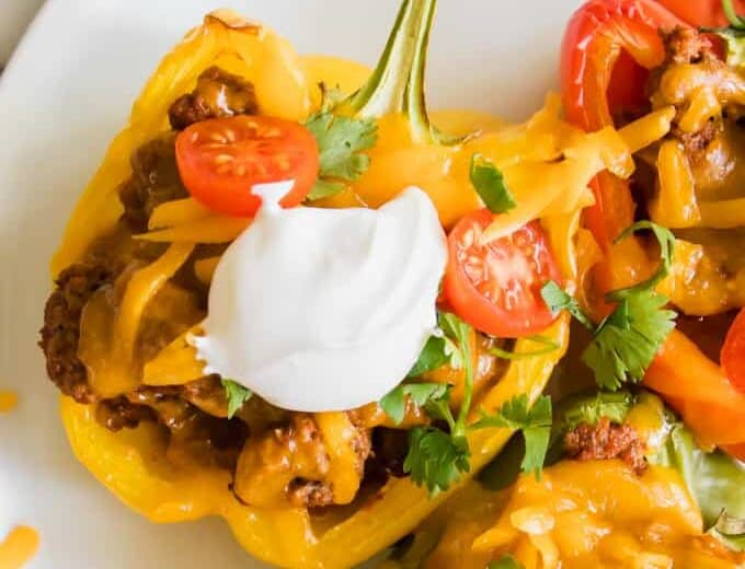 Halved yellow bell pepper filled with ground beef taco meat, cheese, sour cream and tomatoes.