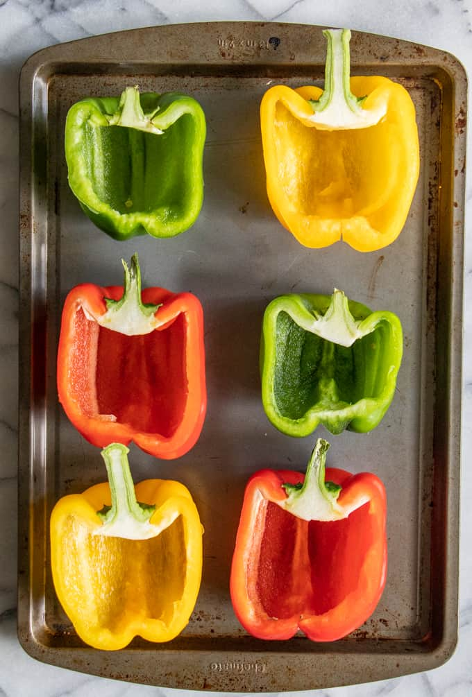 Halved bell peppers on a baking tray with cut sides facing up, ready to bake and make taco stuffed peppers.