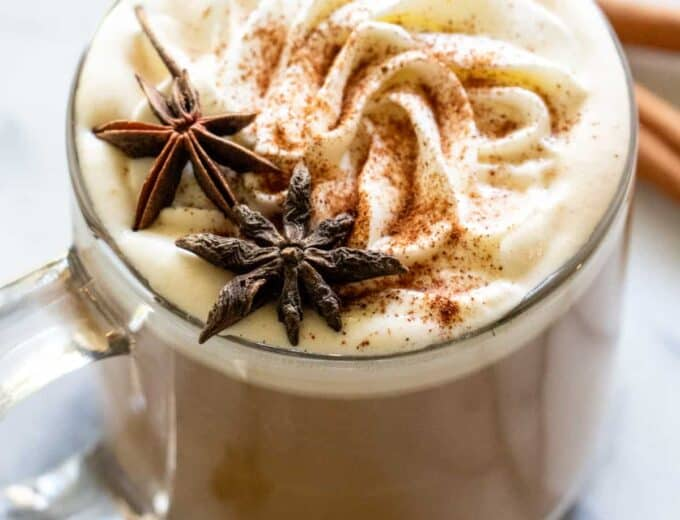 A glass mug filled with apple spice latte, topped with whipped cream and star anise for decoration.