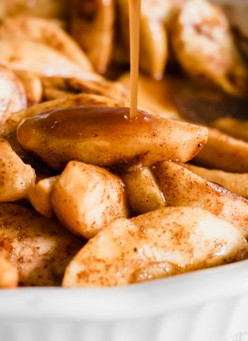 Tender baked apple slices with sauce being drizzled over top.