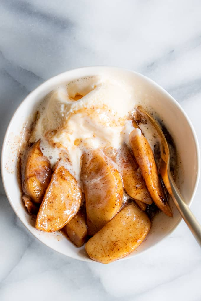 A bowl of baked apples topped with a scoop of vanilla ice cream.