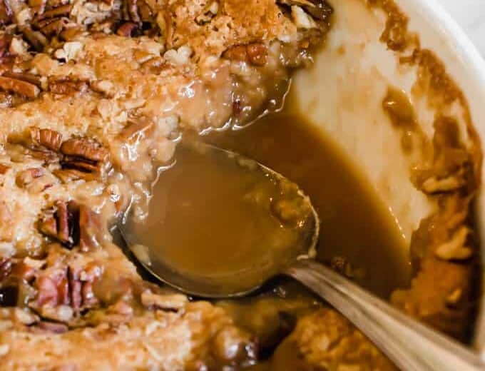 Spoon in a baking dish of pecan cobbler, showing the caramel sauce on the bottom.