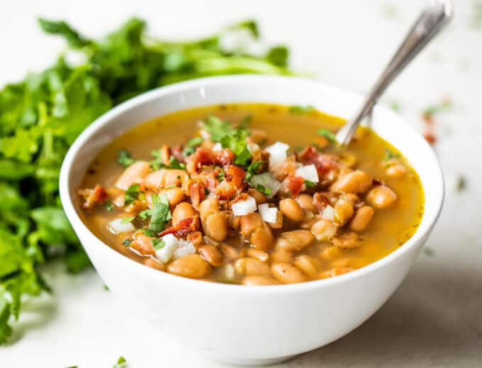Bowl of charro beans served with a spoon.