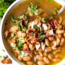 Overhead view of charro beans topped with crisp bacon and diced onion.