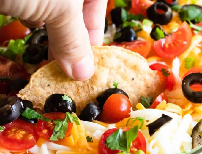 Chip scooping up seven layer dip.