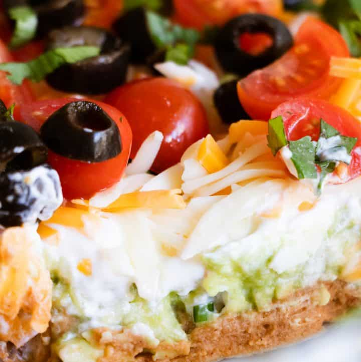 7 layer dip showing refried beans, guacamole, sour cream, cheese, tomato, olives and green onion.