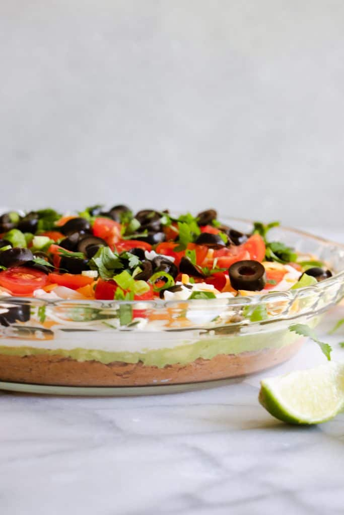A glass pie dish showing the layers in 7 layer dip.