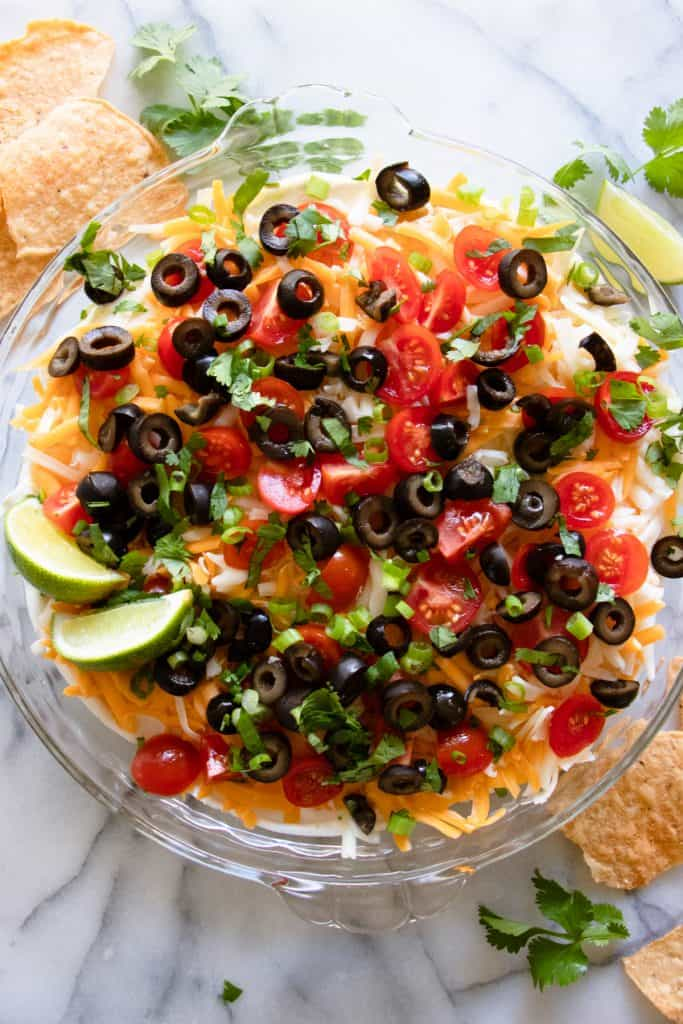 Finished 7 layer dip, garnished with fresh cilantro and lime wedges.